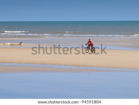 A man riding a bicycle on a seashore - stock photo