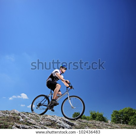 A man riding a mountain bike on a slope, Macedonia - stock photo
