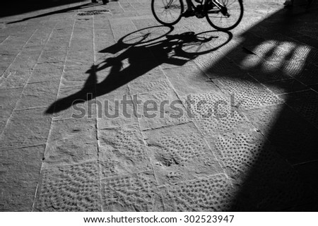 A man riding bicycle silhouette in sunset - stock photo