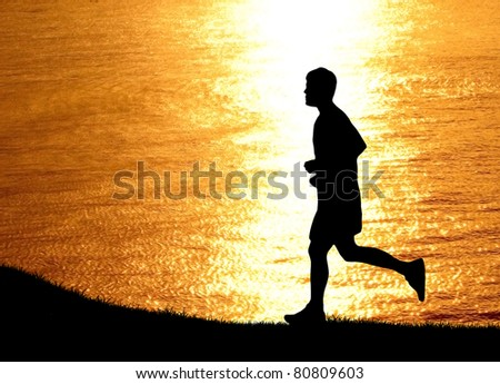 a man run at beach during sunset silhouetted - stock photo