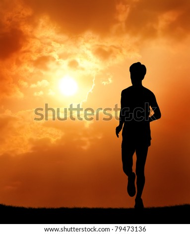 a man running at sunset silhouetted - stock photo
