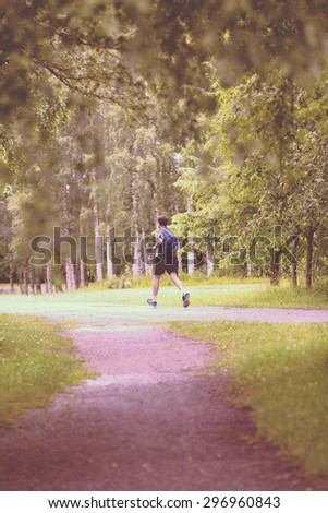 A man running in the rain. Image has a vintage effect. - stock photo