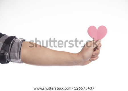 A man's arm reaches out and holds a pink cut out construction paper heart. - stock photo