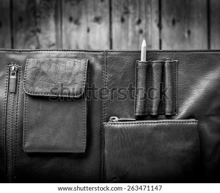 A man's business briefcase bag, leather satchel with a pencil in black and white - stock photo