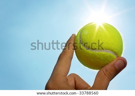 A man's hand holding a tennis ball up to a blue sky with the sun behind it. - stock photo