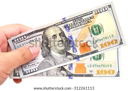 A man's hand holding one hundred dollar bills. - stock photo