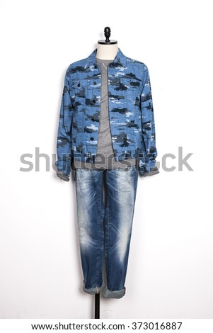 A man's military blue jacket and blue denim(jeans, trousers) with mannequin on the wall isolated white.  - stock photo