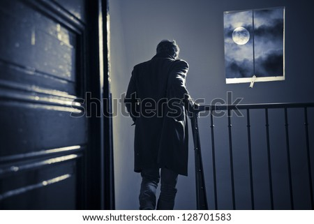 A man seen from behind is going down the staircase in an old parisian building at night. Spooky moon and clouds in the window. - stock photo