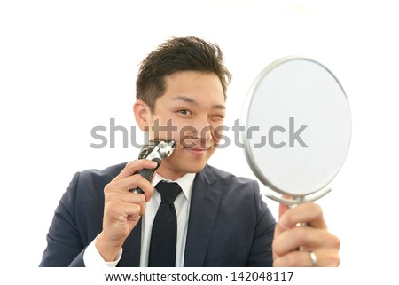 A man shaving with electric razor - stock photo