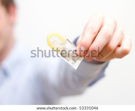 A man showing a condom - stock photo