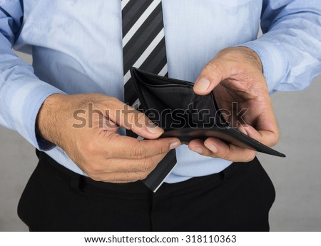 A man showing an empty wallet no money.  Bankruptcy concept, finances concept, - stock photo