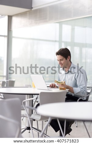 A man sitting at a laptop eating a sandwich - stock photo