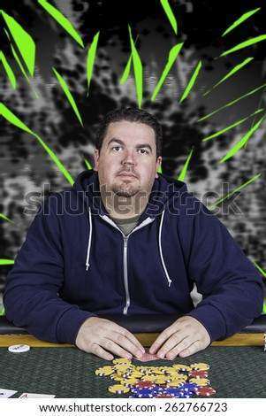A man sitting at a poker table wearing a hoodie gambling playing cards against an abstract background - stock photo