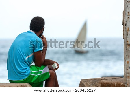 a man sitting contemplating setting sail in a seafaring vessel out in the ocean - stock photo