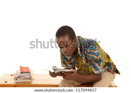 A man sitting on a bench with a stack of books looking at a book with a confused expression on his face. - stock photo