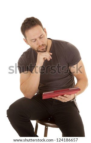 a man sitting on a stool looking at his tablet studying . - stock photo