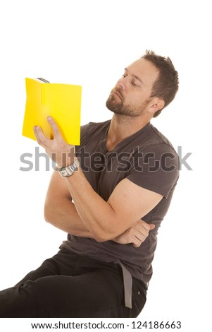A man sitting on a stool reading from his yellow book with a serious expression on his face, - stock photo