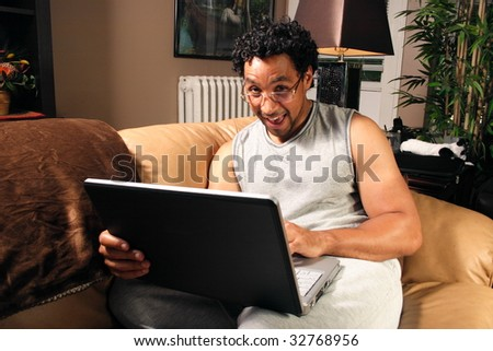 A man sitting on his couch with a laptop smiling at the camera - stock photo