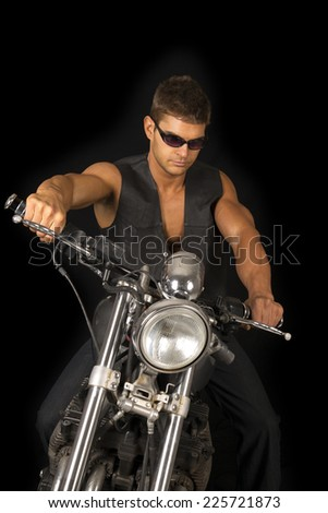 A man sitting on his motorcycle wearing his black vest and sunglasses. - stock photo