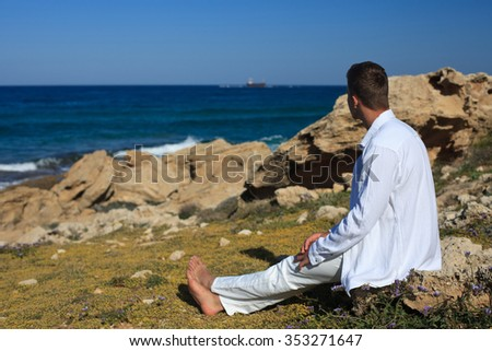 A man sitting on the beach and enjoying the beautiful scenery. close-up  - stock photo