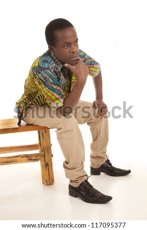 A man sitting on the edge of a bench thinking about something. - stock photo
