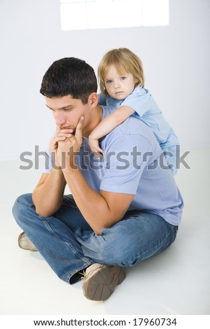 A man sitting on the floor with cross-legged and his daughter hugging him. A man looks like thoughtful. - stock photo