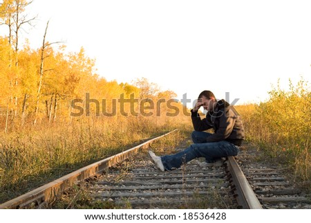 A man sitting on the railroad tracks, sitting in a deep depression - stock photo