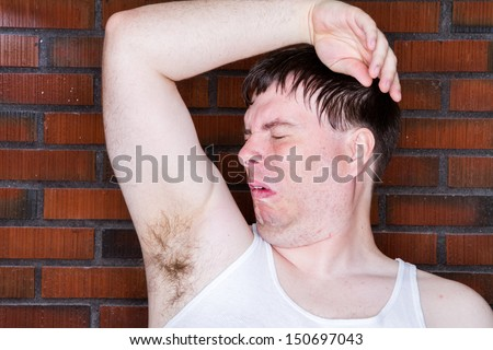A Man sitting there sniffing his arm pit and it stinks. - stock photo