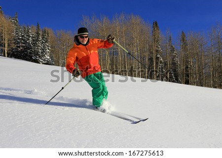 A man skiing fresh powder snow with aspens in the background, Utah, USA. - stock photo