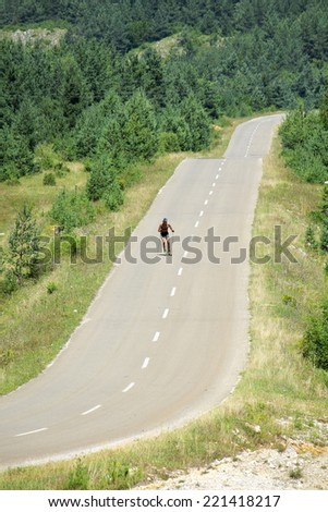 a man skiing with roller ski on a mountain road, Serbia - stock photo