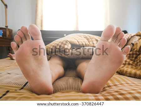 A man sleeping on bed under blanket, in the morning - stock photo