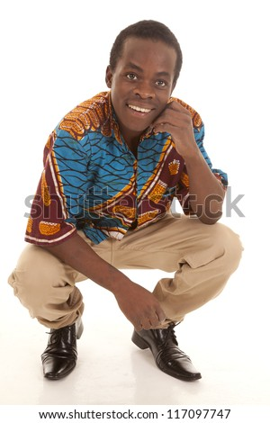 A man squatting down with a smile on his face. - stock photo