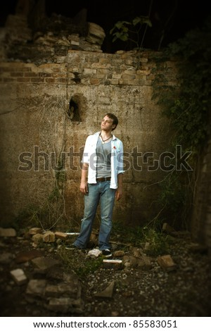 A man standing by an old wall - stock photo