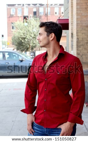 A man standing in the street looking to the side. - stock photo