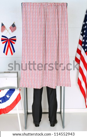 A man standing inside a voting booth at his local polling place. Vertical Format, man is unrecognizable. - stock photo