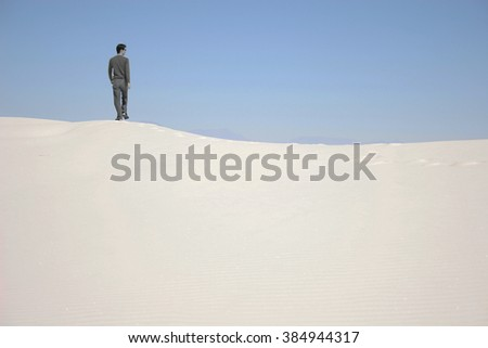 A man standing on a sand dune in White Sands National Monument, New Mexico, USA - stock photo
