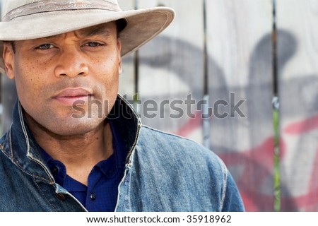 a man stands in front of a wooden fence - stock photo