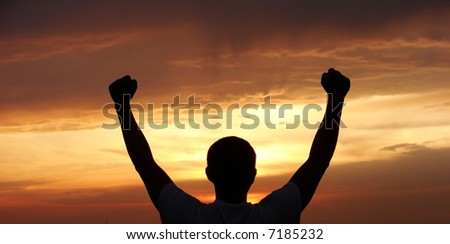 A man stands on against a sun with heaved up hands - stock photo