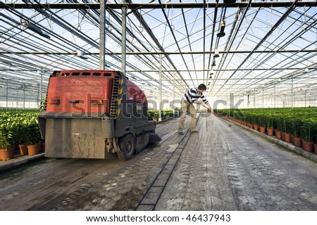 A man sweeping the concrete floor of a huge glasshouse - stock photo