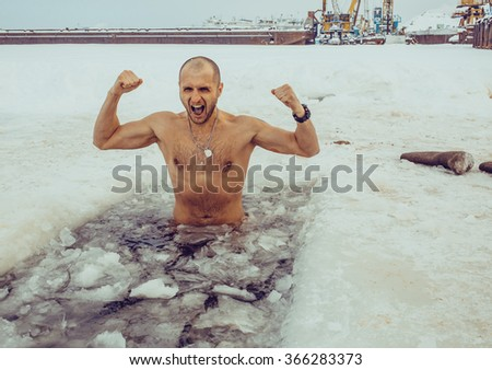 A man swims in the winter - stock photo
