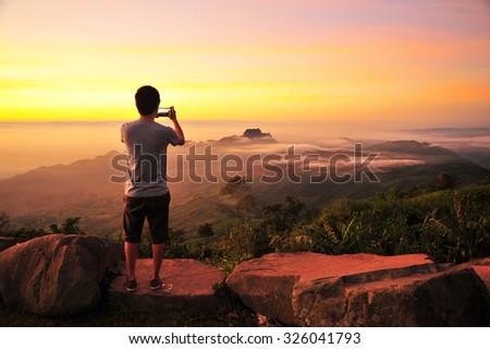 A Man Take Photo of Green Mountain Landscape  - stock photo