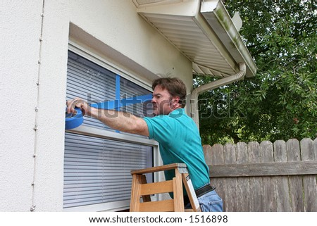 A man taping up his windows to protect from broken glass during a hurricane. - stock photo