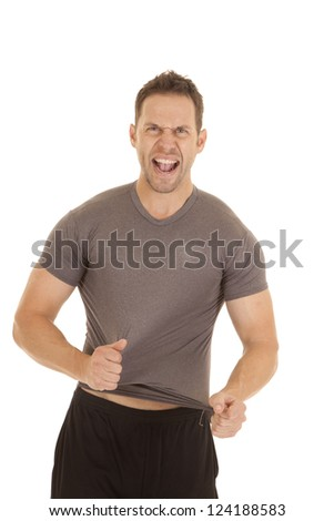 A man trying to rip off his tight fitting shirt. - stock photo