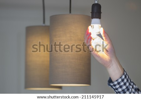 A man turning a lighted lightbulb in his own new house - stock photo