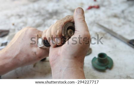 A man twists the upper portion of a sprinkler head. - stock photo