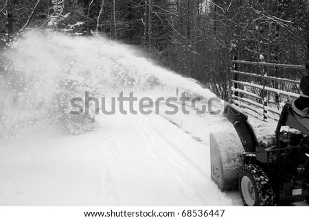 A man using a snow blower to remove snow from driveway. - stock photo