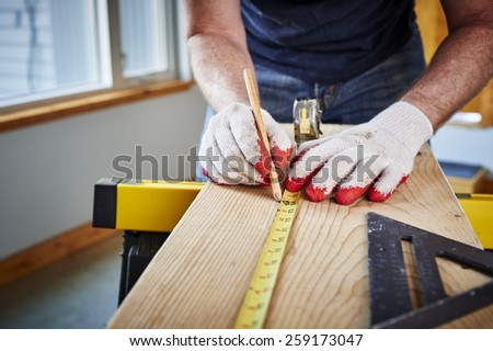 a man using a tape measure and pencil - stock photo