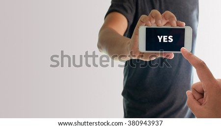a man using hand holding the smartphone with text yes on display - stock photo