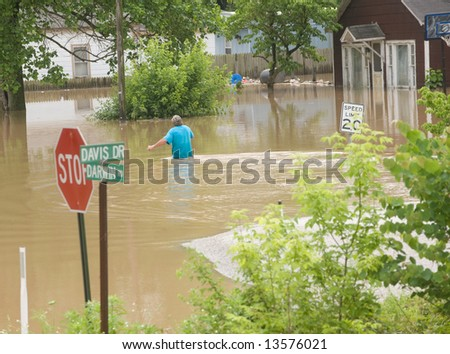 A man wades through flood water in rural Indiana - stock photo