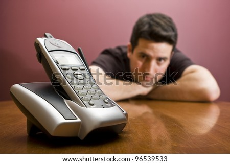 A man waits for the phone to ring - stock photo